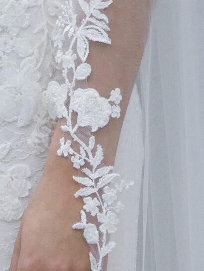 Sluier Randy Fenoli. Enkellaag van zachte tule met een geborduurd bloemenkantpatroon versierd met parels en pailletten. Kant begint bij de elleboog. Lengte 300 cm. Prijs € 210